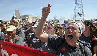 FILE - In this April 10, 2018, file photo, Benita Boone, right, an educator joining on the 110-mile trip from Tulsa to the state Capitol, shouts as the walkers rally with other teachers while protests continue over school funding, in Oklahoma City, Okla. The Oklahoma Supreme Court says an initiative petition that would overturn a package of tax hikes for funding teacher pay raises and public schools is invalid. The court handed down the order Friday, June 22, 2018, and ordered that the initiative petition not appear on the general election ballot in November. (AP Photo/Sue Ogrocki, File)