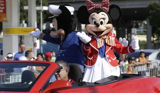 FILE - In this Jan. 12, 2014, file photo, Disney characters Minnie Mouse, right, and Mickey Mouse, rear, ride in the Three Kings Day Parade in Miami. A labor relations panel has upheld most of a judge's ruling that a Teamsters union local representing Disney World workers committed an unfair labor practice when it ignored members' requests to resign from the union. The panel ordered union officials to reimburse some of the former members who had dues deducted after they had made their resignation requests. It also ordered union officials to post notices at its union hall and in Disney World break-rooms informing union members that Local 385 had violated federal labor law. (AP Photo/Wilfredo Lee)
