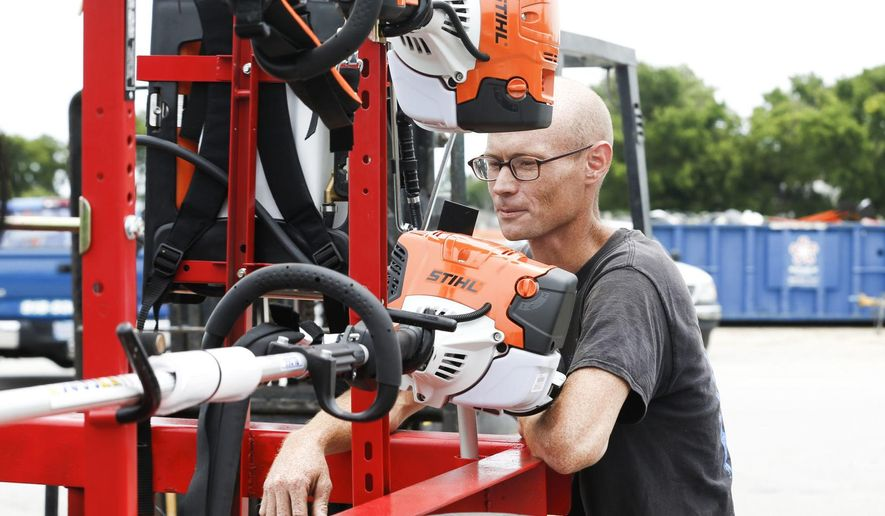 Cody Nichols appraises the new equipment he received from Soldier's Wish at Bloss Equipment in Tulsa, Okla., on Friday, June 22, 2018.  Nichols, a veteran whose life and business were disrupted when his lawn equipment was stolen received $15,000 worth of new lawn-mowing equipment through the nonprofit group Soldier's Wish. The Tulsa-based organization works to meet the needs of military veterans.  (Morgan Hornsby /Tulsa World via AP)