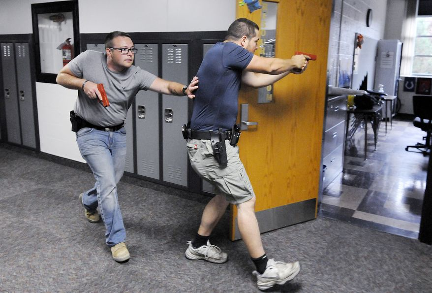 Justin Royse, left, and Dakota Steele practice moving down a hallway during active shooter training at Daleville High School in Daleville, Ind. on Saturday, June 23, 2018. The training included local officers and teachers from the school district. (Don Knight)/The Herald-Bulletin via AP)