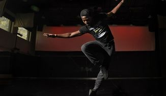 In this June 15, 2018 photo University of Montana graduate Tsiambwom Akuchu preforms in Missoula, Mont. Akuchu recently performed a solo dance he choreographed at the Kennedy Center in Washington, D.C., during the national festival of the American College Dance Association. His dance piece traces the history of black dance and cultural resistance from its African roots to contemporary hip-hop.  (Tommy Martino /The Missoulian via AP)
