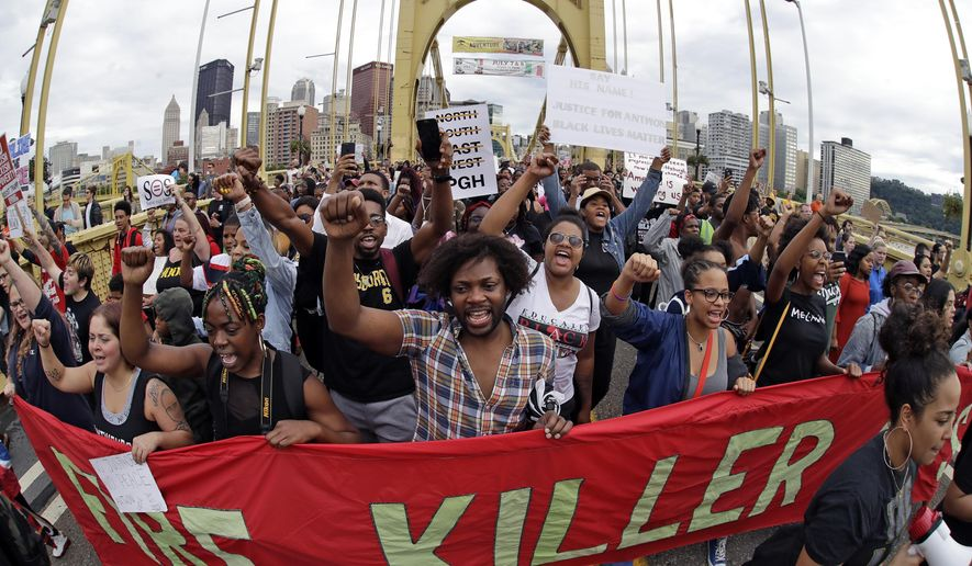 Protestors cross the Roberto Clemente bridge during a evening rush hour march that began in downtown Pittsburgh Friday, June 22, 2018. They are protesting the killing of Antwon Rose Jr. who was fatally shot by a police officer seconds after he fled a traffic stop late Tuesday, in the suburb of East Pittsburgh. (AP Photo/Gene J. Puskar)