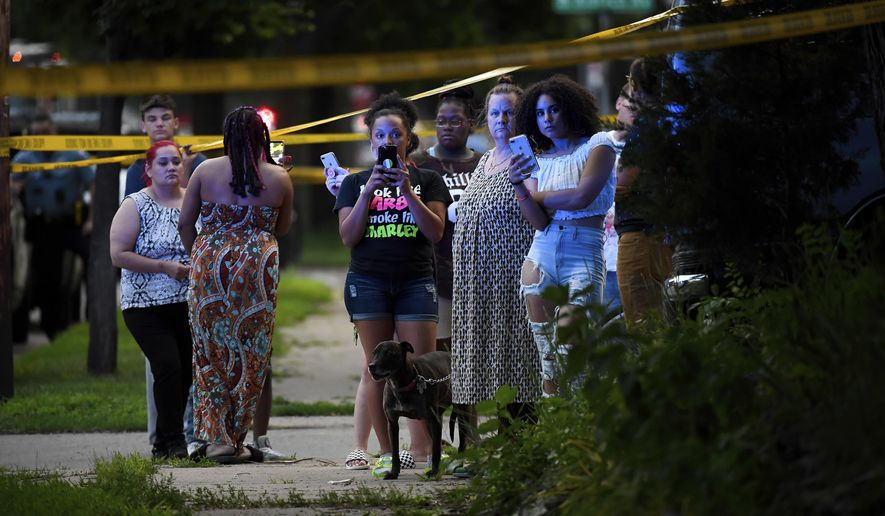 A crowd gathers near the scene of an officer-involved shooting which took place a few hours earlier Saturday, June 23, 2018, in Minneapolis. Police in Minneapolis say officers shot and killed a man who was firing a handgun as he walked down a city street. (Aaron Lavinsky/Star Tribune via AP)