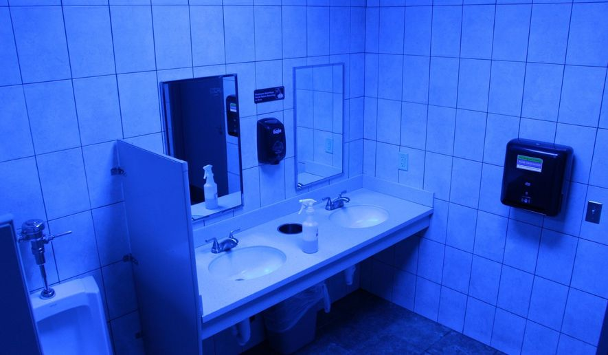 In this June 22, 2018 photo, a public bathroom bathed in blue light is seen at this Turkey Hill convenience store in Wilkes-Barre, Pa. The chain has installed the blue light bulbs in as many as 20 stores in hopes of discouraging drug use by making it harder for people to see their veins. (AP Photo/Michael Rubinkam)