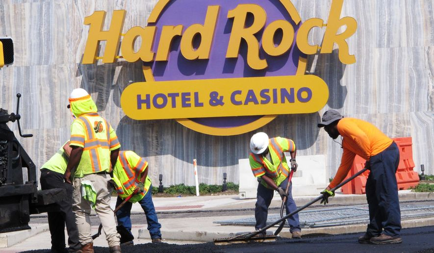 In this June 18, 2018 photo workers rake asphalt outside the Hard Rock casino in Atlantic City, N.J. With the former Revel due to reopen as the Ocean Resort Casino, and the former Trump Taj Mahal due to reopen as the Hard Rock - both on the same day, June 28 - crews are scrambling to get both properties ready for their grand openings. (AP Photo/Wayne Parry)