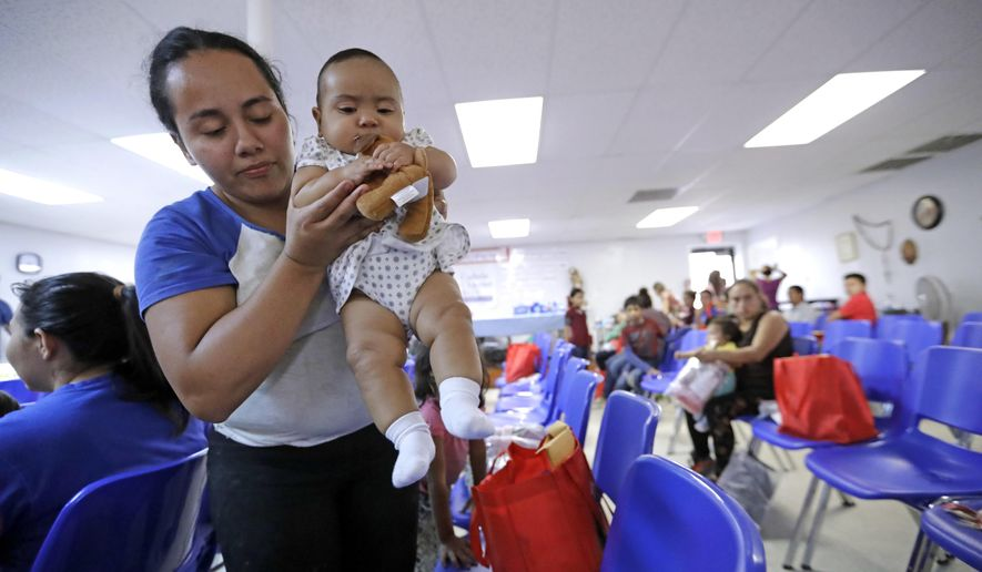 An immigrant woman from Honduras carries her baby inside the Catholic Charities of the Rio Grande Valley on Saturday, June 23, 2018, in McAllen, Texas. Families, who have been processed and released by U.S. Customs and Border Protection, wait inside the facility before continuing their journey to cities across the United States. (AP Photo/David J. Phillip)
