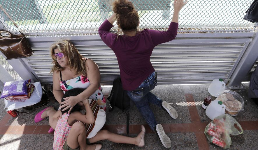 Immigrants from Honduras seeking asylum wait on the Gateway International Bridge, which connects the United States and Mexico, in Matamoros, Mexico on Sunday, June 24, 2018. The family has been waiting two days on the bridge to enter the United States to seek asylum. (AP Photo/David J. Phillip)