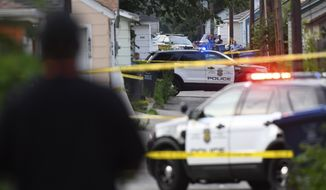 Police investigate the scene of an officer-involved shooting Saturday, June 23, 2018, in Minneapolis. Police in Minneapolis say officers shot and killed a man who was firing a handgun as he walked down a city street. Authorities say two calls to 911 reported that a man was firing a handgun into the air and the ground. (Aaron Lavinsky/Star Tribune via AP)