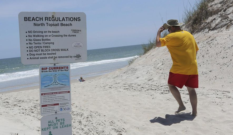 FILE- In this June 2, 2014, file photo, signs warn beach goers about rip currents in additions to regulations along North Topsail Beach at a public access along New River Inlet Drive  in Onslow County, N.C. In a month where 25 people were pulled from the water in one day off the Carolinas' coasts, rescuers are emphasizing the need for both visitors and residents to be aware of the dangers of rip currents. (John Althouse/The Jacksonville Daily News via AP)