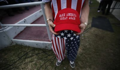 "A man dressed in American flag clothes holds ""Make America Great Again"" hats before President-elect Donald Trump speaks at a rally at the LaddPeebles Stadium, Saturday, Dec. 17, 2016, in Mobile, Ala. (AP Photo/Brynn Anderson) ** FILE ** **FILE**"