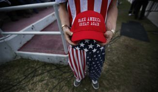 "A man dressed in American flag clothes holds ""Make America Great Again"" hats before President-elect Donald Trump speaks at a rally at the LaddPeebles Stadium, Saturday, Dec. 17, 2016, in Mobile, Ala. (AP Photo/Brynn Anderson) ** FILE **"
