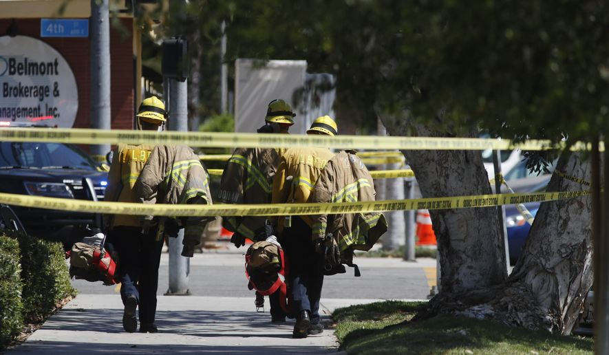 Long Beach firefighters walk along a street near a retirement home where at least one firefighter was killed in Long Beach, Calif., on Monday, June 25, 2018. A resident of the retirement home in Southern California opened fire on firefighters responding to a report of an explosion in the building, officials said. (AP Photo/Jae C. Hong)