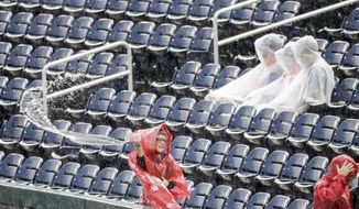 Spectators wait in the rain as a youth bails water from the stands, during a rain delay before Game 1 of the NCAA College World Series baseball finals between Oregon State and Arkansas, in Omaha, Neb in Omaha, Neb., Monday, June 25, 2018. Game 1 has been rescheduled for Tuesday. (AP Photo/Nati Harnik)