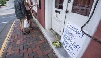 "Passersby examine the menu at the Red Hen Restaurant Saturday, June 23, 2018, in Lexington, Va. White House press secretary Sarah Huckabee Sanders said Saturday in a tweet that she was booted from the Virginia restaurant because she works for President Donald Trump. Sanders said she was told by the owner of The Red Hen that she had to ""leave because I work for @POTUS and I politely left."" (AP Photo/Daniel Lin)"