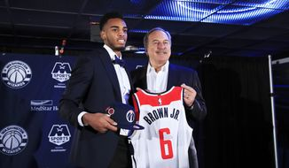 Washington Wizards Troy Brown Jr., the team's first-round pick in the 2018 NBA draft, and general manager Ernie Grunfeld, pose for pictures as Brown is introduced during a news conference in Washington, Monday, June 25, 2018. (AP Photo/Manuel Balce Ceneta)