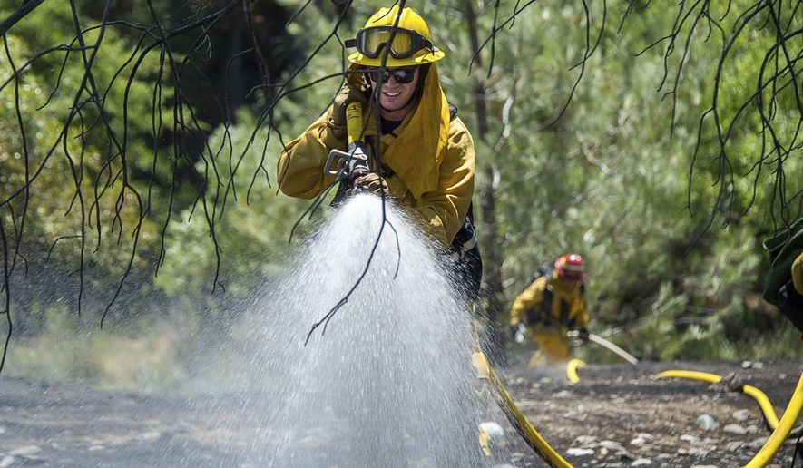 Fire crews battle the Pawnee Fire on Cache Creek Road on Monday, June 25, 2018 in Spring Valley, Calif. Thousands were forced to flee their homes Monday as major wildfires encroached on a charred area of Northern California still recovering from severe blazes in recent years, sparking concern the state may be in for another destructive series of wildfires this summer.  (Paul Kitagaki Jr./The Sacramento Bee via AP)