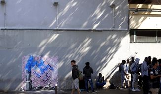 A graffiti believed to be attributed to street artist Banksy is seen on the wall by a group of migrants, in Paris, Monday, June 25, 2018. Seven works attributed to the graffiti artist have been discovered in recent days, including one near a former center for migrants at the city's northern edge, according to the art website Artistikrezo.  (AP Photo/Thibault Camus)