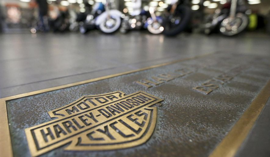In this April 26, 2017, file photo, rows of motorcycles are behind a bronze plate with corporate information on the showroom floor at a Harley-Davidson dealership in Glenshaw, Pa. Harley-Davidson, facing rising costs from new tariffs, will begin shifting the production of motorcycles heading for Europe from the U.S. to factories overseas. (AP Photo/Keith Srakocic, File)