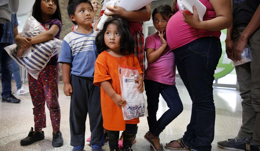 Ingrid Yanet Lopez Hernandez, 32, center back, her children Jazmine, 7, from left, Christian, 5, and Cristle Ordonez, 2, and pregnant mother Meregilda Mejilla, 27, and her daughter Maricelda Mejilla, 6, wait after being processed by the U.S. Border Patrol and then dropped off at the Central Station bus terminal in downtown McAllen, Texas, Sunday, June 24, 2018. From there the families were gathered up by the Catholic Charities of the Rio Grande Valley and walked to their location a few blocks away. There they would get cleaned up, fed and receive help getting transportation to their future destinations. (Tom Fox/The Dallas Morning News via AP) **FILE**