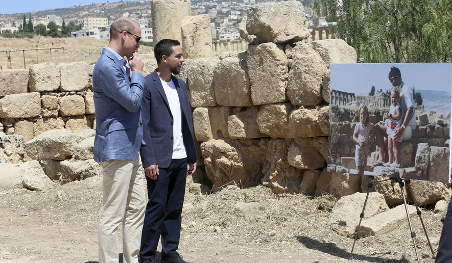 Britain's Prince William and Jordanian Crown Prince Hussein look at a photograph showing William's wife, the former Kate Middleton, her father Michael and younger sister Pippa in the ruins of the Roman city of Jerash in the 1980s in Jerash, Jordan, Monday, June 25, 2018. (AP Photo/Raad al-Adayleh)