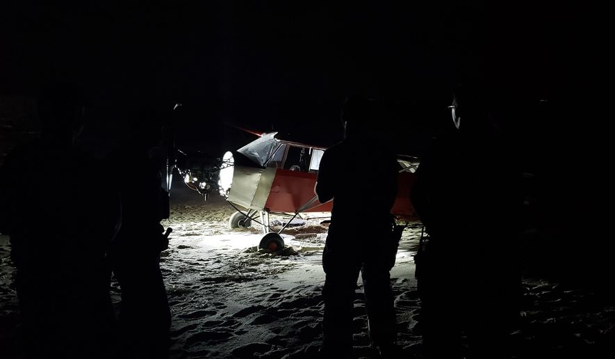 In this June 24, 2018 photo, Coast Guard personnel stand in front of a plane on a secured beach on the southeast side of Training Center Cape May in Cape May, N.J., after it landed illegally and there was no sign of the pilot. The Coast Guard says officers became aware of the incident when the plane was spotted on closed-circuit cameras. (Petty Officer 2nd Class Richard/U.S. Coast Guard via AP)