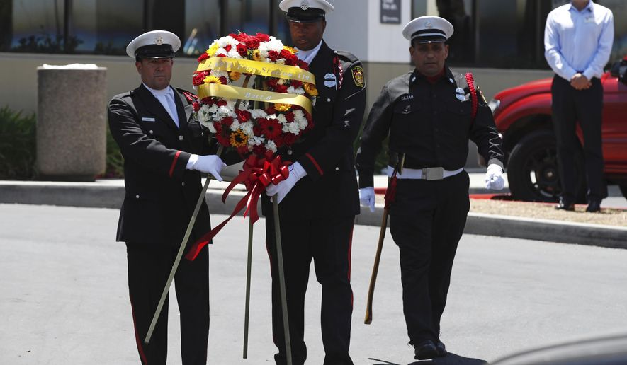 Long Beach firefighter honor guard carry a wreath outside Saint Mary Medical Center prior to a procession for Fire Capt. Dave Rosa who was killed after he was shot responding to an emergency at a senior home in Long Beach, Calif., on Monday, June 25, 2018. A resident of a retirement home in Southern California opened fire on firefighters responding to a report of an explosion in the building, killing Rosa, and wounding others. (AP Photo/Jae C. Hong)