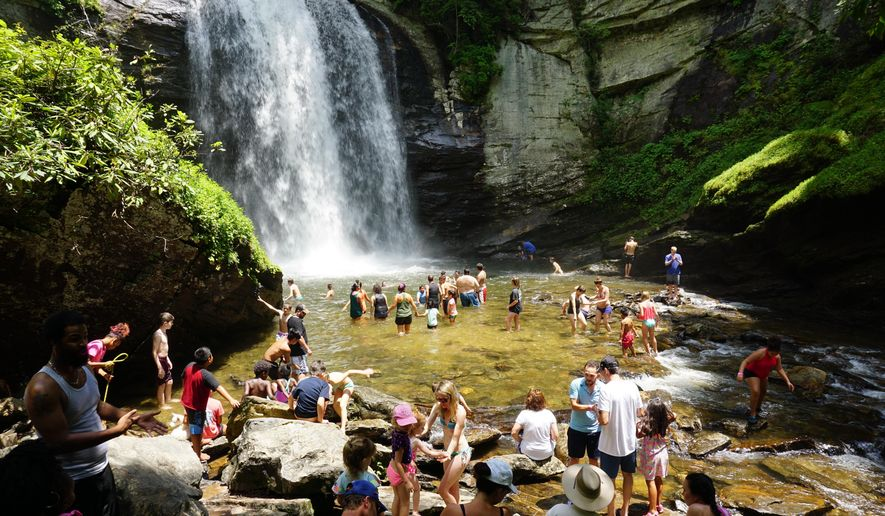 """This May 18, 2018 photo shows swimmers wading in at the base of Looking Glass Falls, located in the Pisgah National Forest, between Brevard, N.C., and the Blue Ridge Parkway. Known as """"The Land of the Waterfalls,"""" Transylvania County boasts more than 250 waterfalls that attract visitors every year. (Hillary Speed via AP)"""