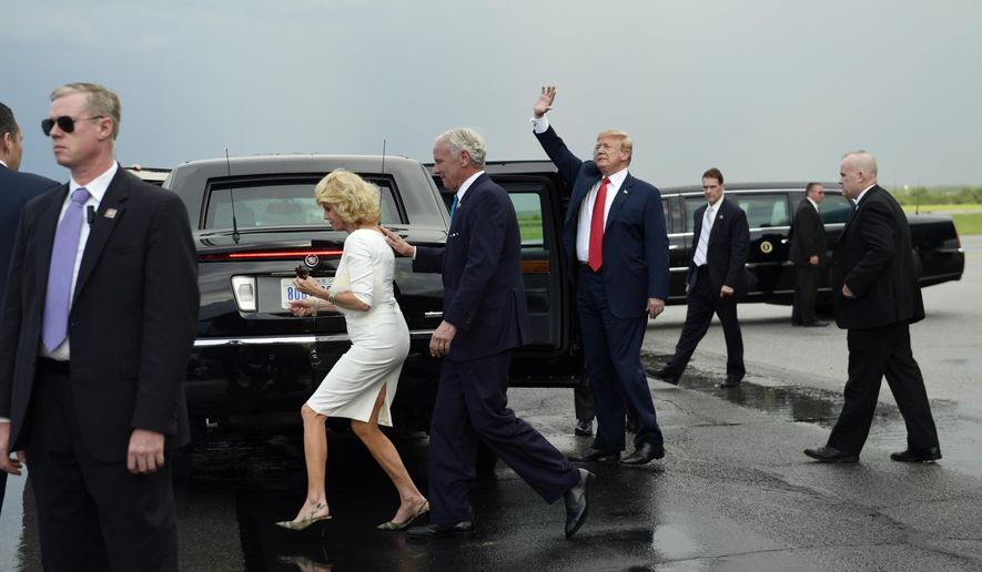 President Donald Trump waves at Columbia Metropolitan Airport in West Columbia, S.C., Monday, June 25, 2018, as Republican Gov. Henry McMaster and his wife Peggy walk behind the car. (AP Photo/Susan Walsh)