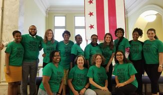 "Members of the ""Birth to Three Policy Alliance"" waited in matching shirts outside the D.C. Council chambers Tuesday and cheered when they heard that the council unanimously approved legislation funding early childhood education iniatitives they had supported for the 10 years. (Julia Airey/ The Washington Times)"