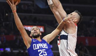 Los Angeles Clippers guard Austin Rivers, left, shoots as Washington Wizards center Marcin Gortat, of Serbia, defends during the first half of an NBA basketball game, Saturday, Dec. 9, 2017, in Los Angeles. The pair was reportedly traded for one another on Tuesday with Rivers going to the Wizards and Gortat sent to Los Angeles (AP Photo/Mark J. Terrill). **FILE**