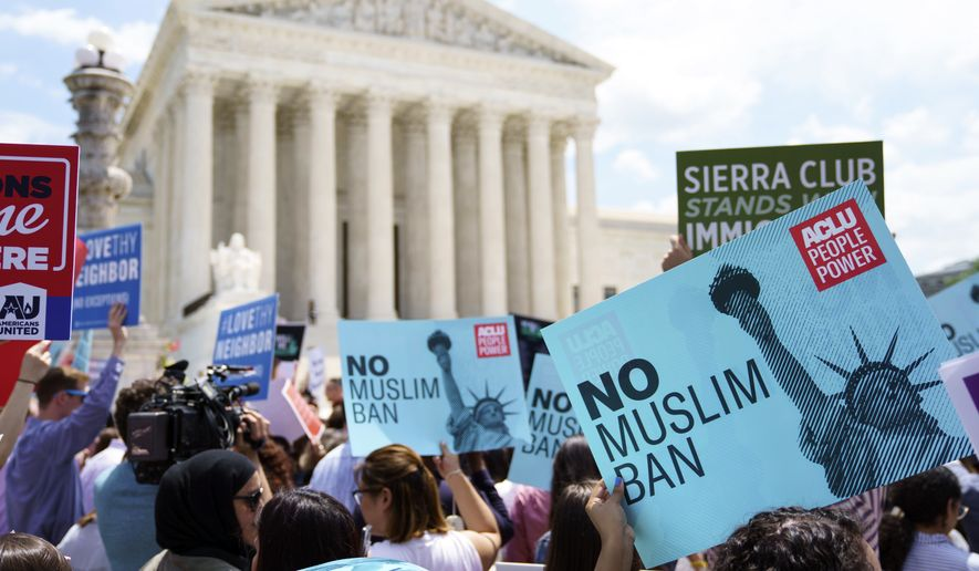 Protesters hold up signs and call out against the Supreme Court ruling upholding President Donald Trump's travel ban outside the the Supreme Court in Washington, Tuesday, June 26, 2018. (AP Photo/Carolyn Kaster)