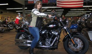 "FILE - In this Dec. 12, 2017, file photo, Terri Meehan poses on a 2018 Harley Softail Slim in Milwaukee's House of Harley. Meehan took a riding course at the dealership as part of Harley-Davidson's ""Riding Academy,"" an initiative the company hopes will help bring new customers. Harley-Davidson, the iconic brand that sells its customers an image of freedom and adventure, found itself in an unwanted role this week: poster child for the damage of an international trade war. Harley said it would move production of motorcycles bound for Europe overseas, blaming European Union tariffs it said would add an estimated $2,200 cost to the average bike.(AP Photo/Ivan Moreno, File) **FILE**"