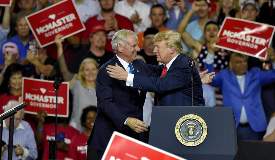 President Donald Trump greets Gov. Henry McMaster during a rally to show support for the governor at Airport High School, Monday, June 25, 2018, in West Columbia, S.C. (AP Photo/Richard Shiro)