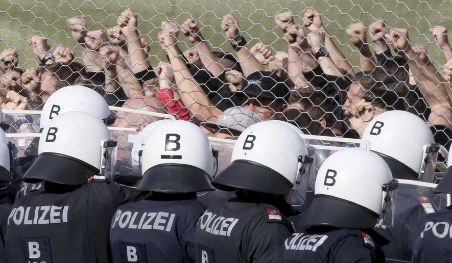 Austrian police stand behind a fence with when they practice the protection of the border between Slovenia and Austria in Spielfeld, Austria, Tuesday, June 26, 2018. (AP Photo/Ronald Zak)