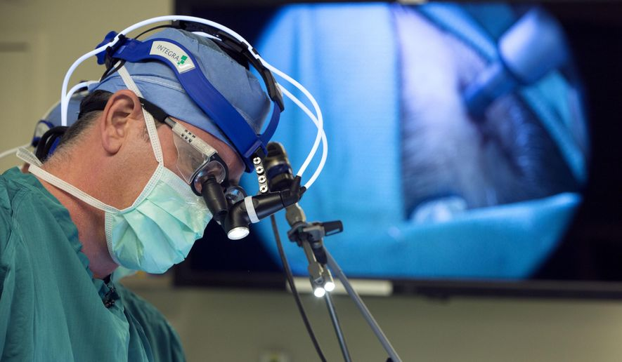 In this Oct. 28, 2014, file photo provided by Duke University, neurosurgeon Dr. John Sampson places a catheter into a glioblastoma patient at Duke in Durham, N.C. One of the world's most dreaded viruses has been turned into an immune system therapy to fight deadly brain tumors. Survival was better than expected for patients in a small study treated with a modified poliovirus, which helped their bodies attack their cancer, doctors reported on Tuesday, June 26, 2018. (Shawn Rocco/Duke Health via AP) ** FILE **