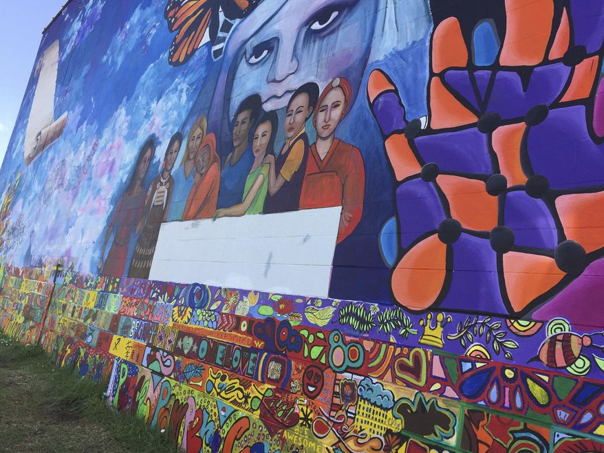 """This Tuesday, June 26, 2018 photo shows where last-minute addition of an immigrant child clinging to her mother has been removed from a mural near the Brown v. Board of Education National Historic site in Topeka, Kan. The Kansas City Star reports that the image was painted over Monday on a 130-foot wide, 30-foot tall mural across from the former all-black school that tells the story of the U.S. Supreme Court ruling that ended segregated education. Artist bj McBride says she """"couldn't help"""" adding the child Friday in response to the separation of parents and children at the U.S. border, but said later she thinks it was """"distracting."""" (AP Photo/Mitchel Willetts)"""