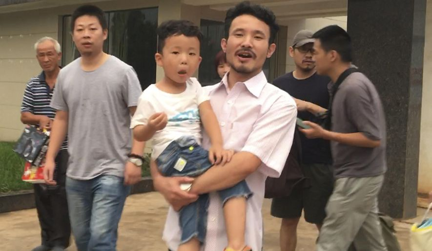 FILE - In this June 28, 2017 file image taken from video, Chinese labor activists Hua Haifeng, center, carries his son Bo Bo, and Li Zhao, second left, leave a police station after being released in Ganzhou in southern China's Jiangxi Province. China Labor Watch says three activists who were arrested while investigating abuses at Ivanka Trump's Chinese suppliers last year were released from bail on Tuesday June 26, 2018, but questions remain about their ability to live and work freely. (AP Photo/Gerry Shih, File)