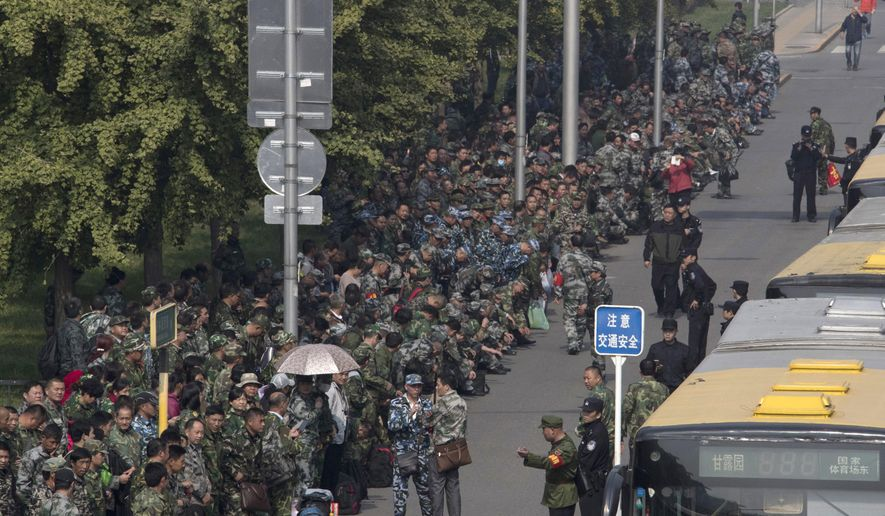 FILE - In this Tuesday, Oct. 11, 2016, file photo, hundreds of protesters in green fatigues gather outside the Chinese Ministry of National Defense to protest in Beijing. On Chinese state television broadcasts, President Xi Jinping is often shown clad in battle fatigues inspecting troops, praising their service, and hailing the People's Liberation Army as key to the country's rising global power. But the nationalist drumbeat rings hollow for many retired soldiers who feel left behind, and they have taken to the streets in droves to complain about having to fend for themselves with meager pensions and little support. (AP Photo/Ng Han Guan, File)