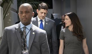 Speaker of the House Paul Ryan, R-Wis., confers with his press secretary AshLee Strong, right, as a member of his protection detail escorts at left, following a closed-door GOP strategy session at the Capitol in Washington, Tuesday, June 26, 2018. Ryan has scheduled a long-awaited showdown vote on a broad Republican immigration bill for Wednesday, but he's showing little confidence that the package will survive. (AP Photo/J. Scott Applewhite)