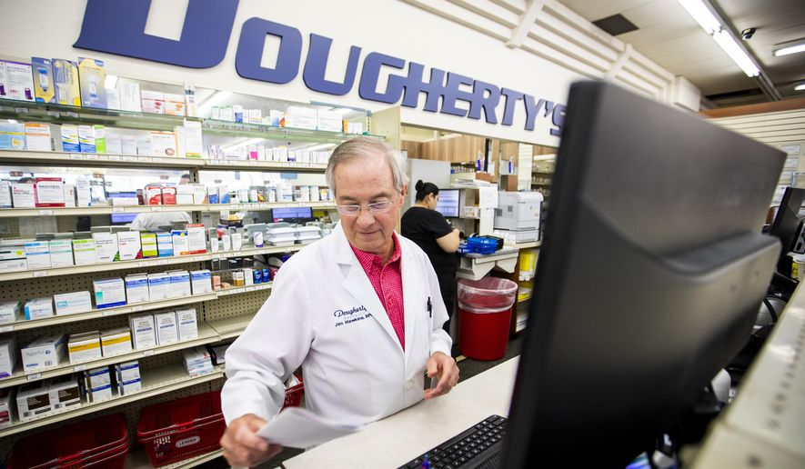 Pharmacist Jim Hawkins works behind the counter at the flagship Dougherty's Pharmacy in Preston Royal Village on Thursday, May 31, 2018, in Dallas. (Smiley N. Pool/The Dallas Morning News via AP) **FILE**