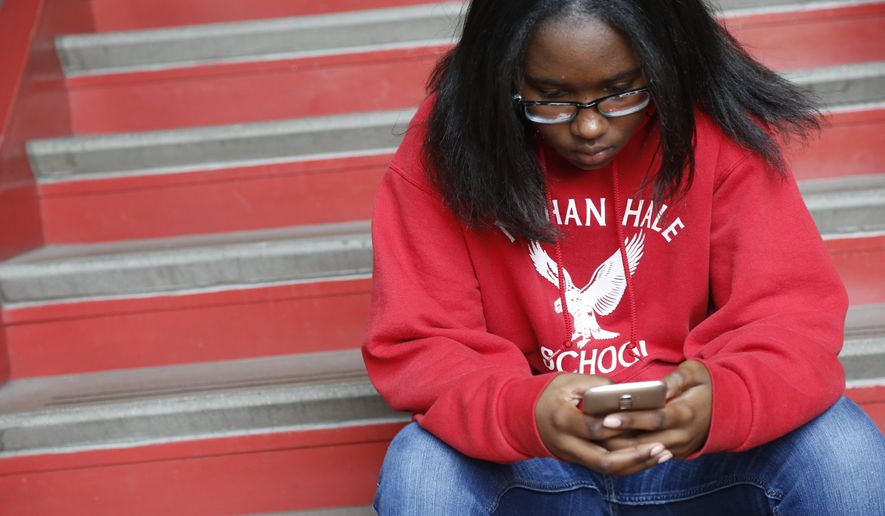 Ayrial Miller, 13, takes a quick moment to check her phone at Nathan Hale Elementary School in Chicago on Friday, June 8, 2018, to show how the monitoring software her mom has installed on the phone works. Most of the school day, students' phones stay with their homeroom teachers. (AP Photo/Martha Irvine)
