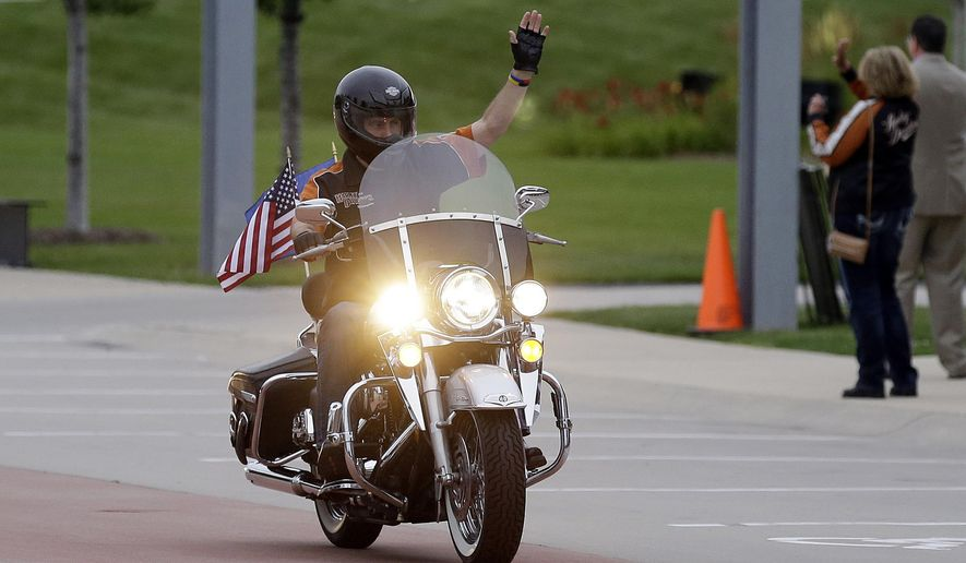"""FILE - In this Aug. 2, 2013 file photo, Wisconsin Governor Scott Walker rides a Harley Davidson motorcycle to the motorcycle museum in Milwaukee. The Republican governor faces revved up criticism of the Milwaukee-based company from President Donald Trump. The president on Tuesday, June 26, 2018, tweeted that if Harley goes through with its plans to move some production overseas, """"it will be the beginning of the end."""" (AP Photo/Jeffrey Phelps, File)"""