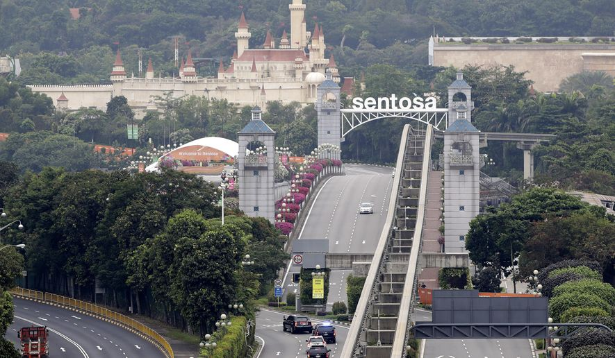 In this June 12, 2018, file photo, a car carrying U.S. President Donald Trump enters Sentosa island where the summit between him and North Korean leader Kim Jong-un will take place at the Capella Hotel in Sentosa, Singapore. (AP Photo/Wong Maye-E, File)