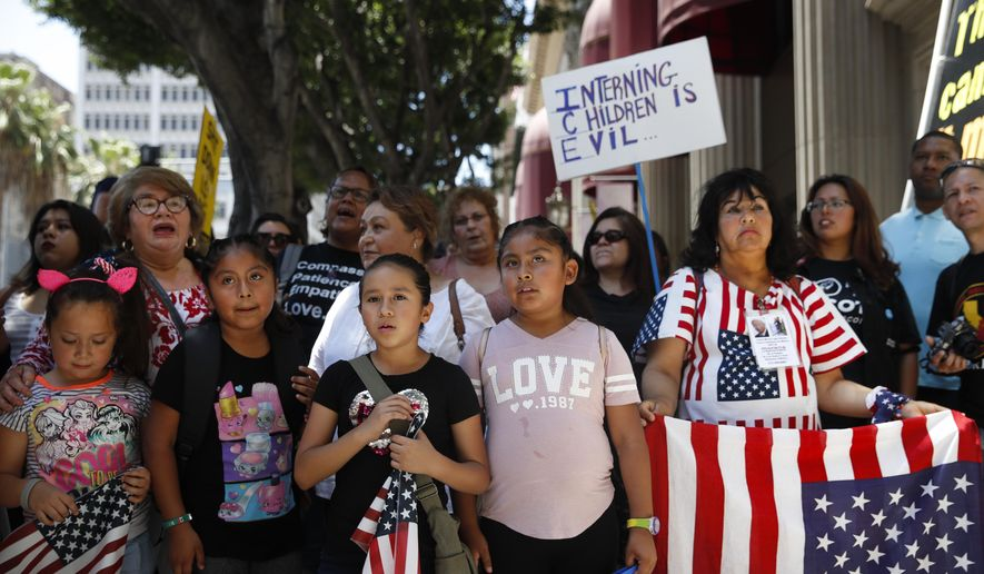 People gather outside the Millennium Biltmore Hotel to protest against U.S. Attorney General Jeff Sessions, Tuesday, June 26, 2018, in Los Angeles. Sessions gave a speech at the hotel. (AP Photo/Jae C. Hong)