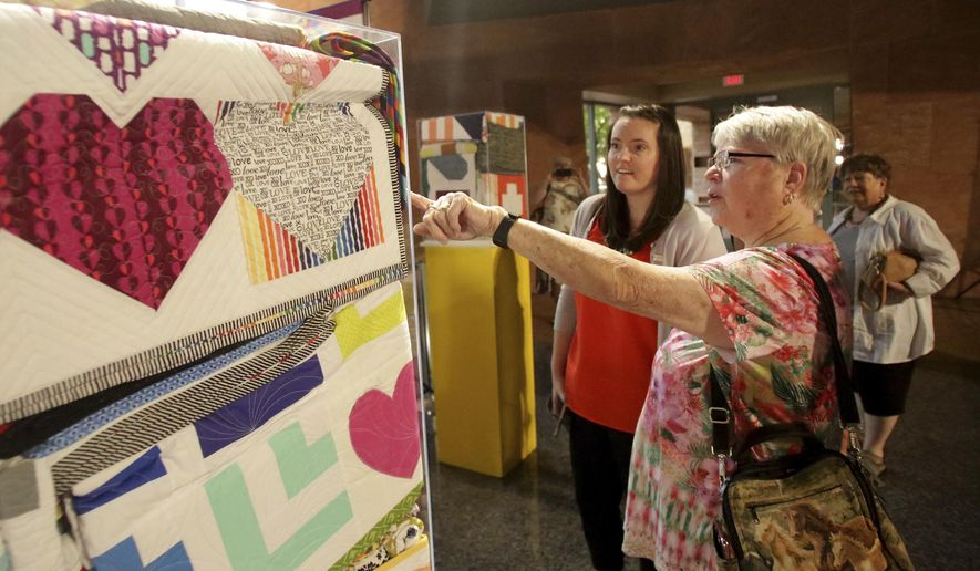 Kathy Farris, right, points out details, to Modern Quilting Guild member Sara Carey, in one of the over 250 quilts that were donated to the Vegas Strong Resiliency Center to help victims of the October 1 shooting during an exhibit at the Clark County Government Center in Las Vegas, Monday, June 25, 2018. (Michael Quine/Las Vegas Review-Journal via AP)