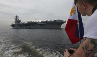 "A U.S. sailor takes photos of the U.S. aircraft carrier USS Ronald Reagan (CVN 76) as it anchors off Manila Bay for a goodwill visit Tuesday, June 26, 2018 west of Manila, Philippines. The U.S. military has deployed the U.S. aircraft carrier to patrol the South China Sea ""to deter conflict and coercion"" in a disputed region where Washington has moved against China's military buildup on manmade islands. (AP Photo/Bullit Marquez)"