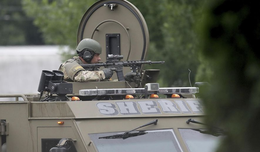 A sheriff's department SWAT team member keeps an eye toward the apartment where a man is barricaded Tuesday, June 26, 2018, in New Hope, Minn. A tense standoff in a New Hope, Minn., apartment between law enforcement and a man believed to be holding two children, and possibly a weapon, has stretched into Tuesday morning.  (David Joles/Star Tribune via AP)