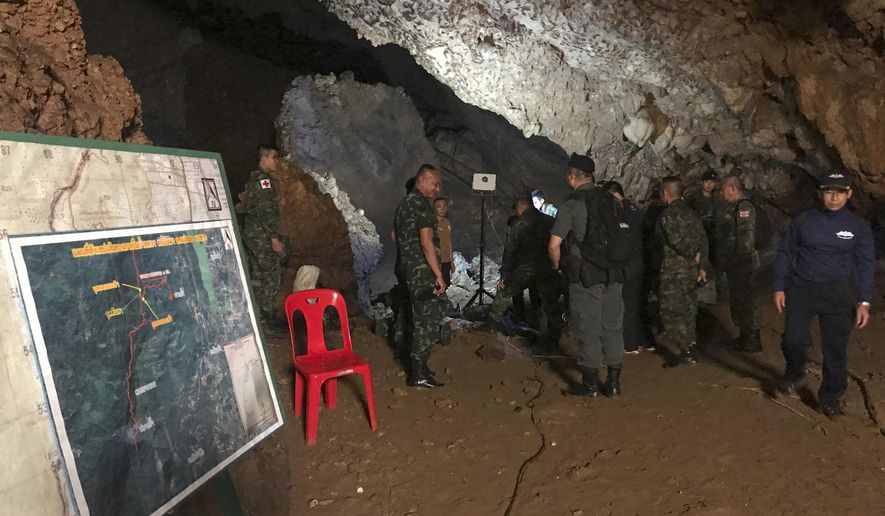 Rescue workers continue to search for a group of missing boys and their coach in a flooded cave, Tuesday, June 26, 2018, in Mae Sai, Chiang Rai province, northern Thailand. Electricians are extending a power line into a flooded cave in northern Thailand to help the search and rescue efforts for 12 boys and their soccer coach stranded three nights in the sprawling caverns and cut off by rising water. (AP Photo/Tassanee Vejpongsa)