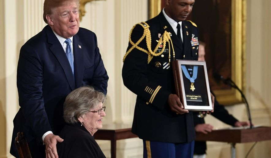 """President Donald Trump speaks before he awards the Medal of Honor to 1st Lt. Garlin Conner as his widow Pauline Connor accepts the posthumous recognition, during a ceremony in the East Room of the White House in Washington, Tuesday, June 26, 2018. Conner is being recognized for actions on Jan. 24, 1945, when he left a position of relative safety for a better position """"to direct artillery fire onto the assaulting enemy infantry and armor."""" Conner remained in an exposed position for three hours, despite German forces coming within five yards of his position and friendly artillery shells exploding around him. (AP Photo/Susan Walsh)"""