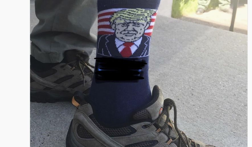 """This screen shot posted Tuesday, June 26, 2018, on the official Twitter account of U.S. Interior Secretary Ryan Zinke shows him wearing socks with an image of President Trump and the campaign slogan """"Make America Great Again,"""" which has been blacked out on the photo, during an official event in Keystone, S.D. After critics said the unaltered image could be a violation of the Hatch Act, he blacked out the slogan and reposted the image with an apology. (U.S. Interior Department via AP)"""